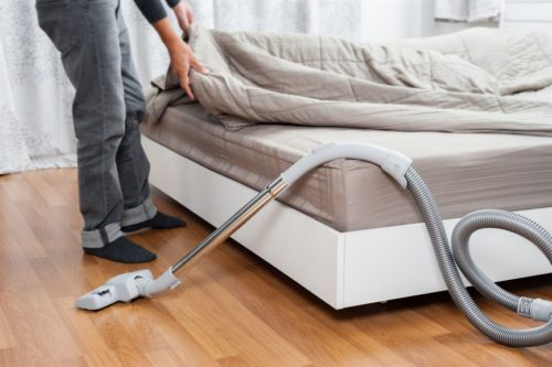 Person changing duvet on a bed. Next to them is a hoover.