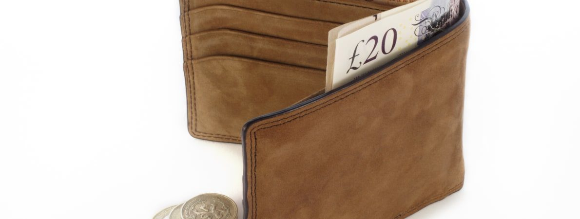 Photo of man's wallet with paper notes and coins.