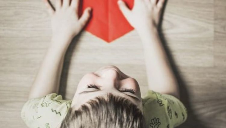 Photo of child holding red paper heart.