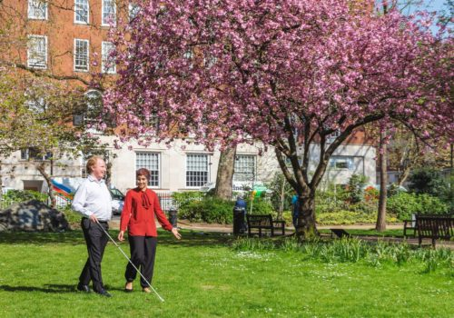 Blind man with a cane holding a woman by the arm in the park.