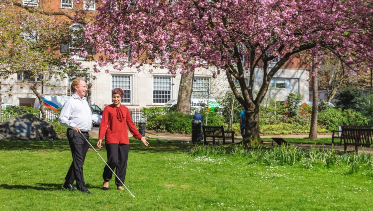 Man with cane walking in park with lady in sunshine