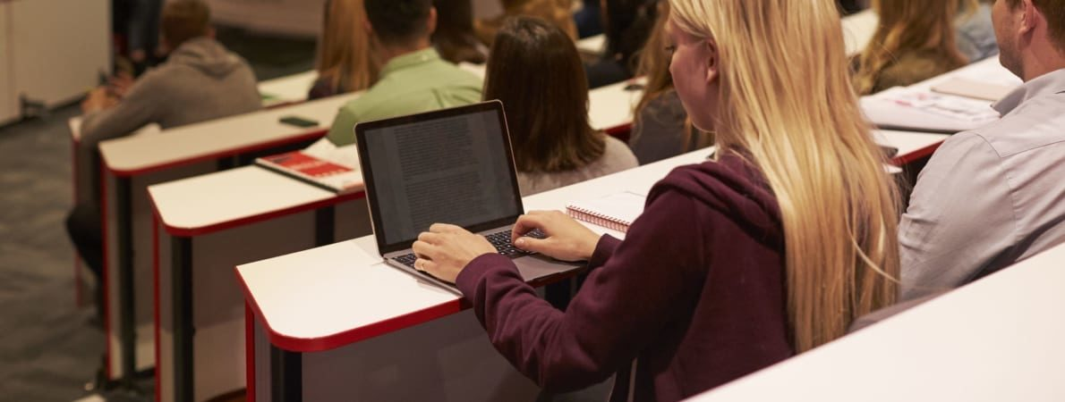 Photo of woman typing on laptop in lecture hall.