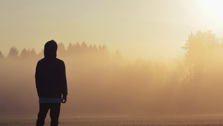 Teenage boy facing away from the camera. The sun is setting behind him