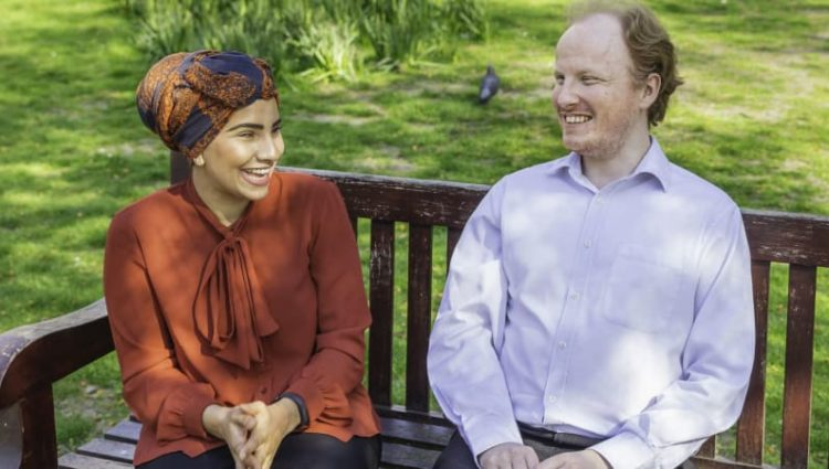 Photo of man and woman chatting on bench.