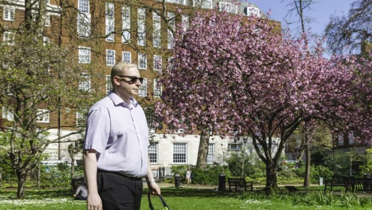 Man with cane walking in park