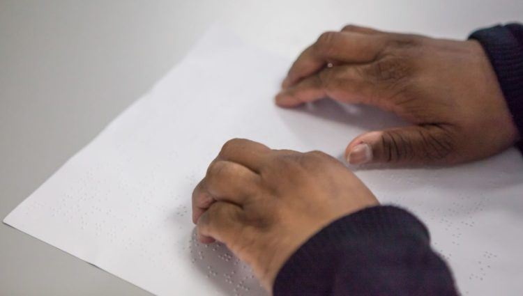 close up of hands on Braille