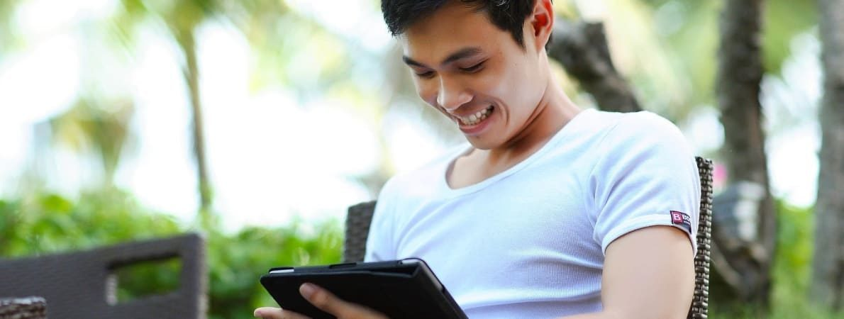 Student smiling using iPad