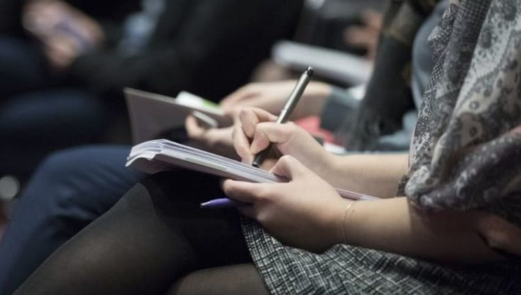 People taking notes at an event