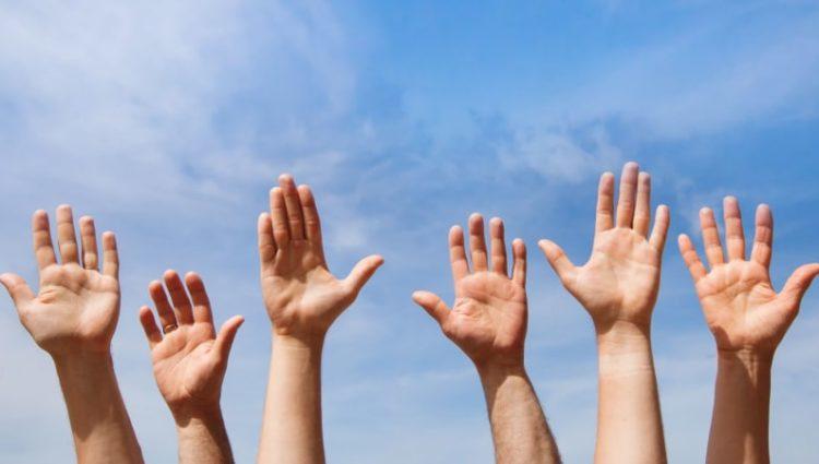 Raised hands on blue sky