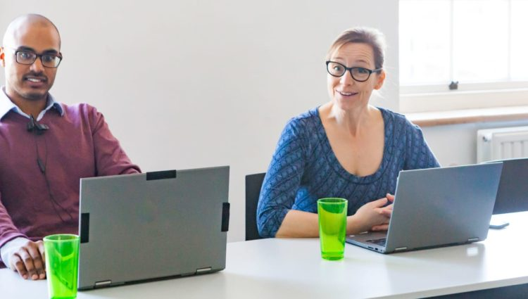 Man and woman at conference table with laptops