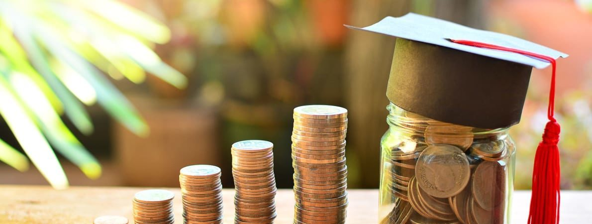Photo of money in piles with a mortar board