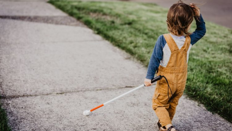 Vision impaired child in yellow dungarees walking along the pavement with a cane