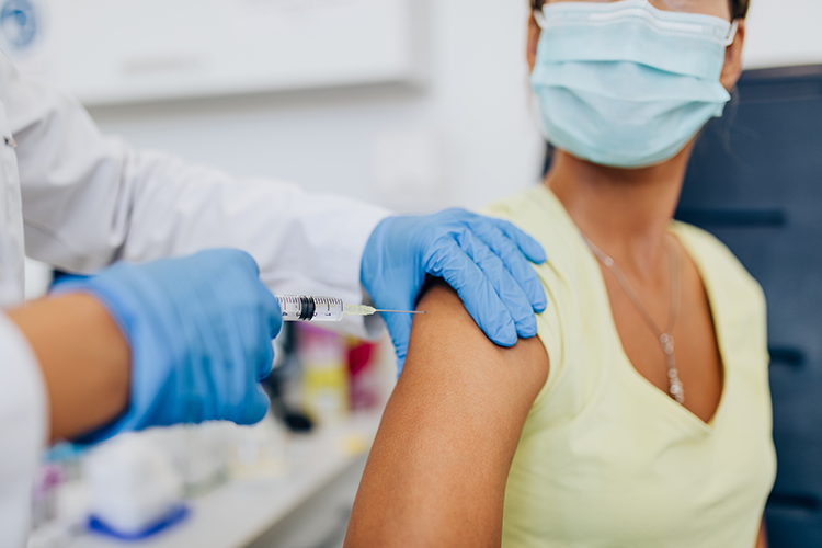 Female doctor or nurse giving shot or vaccine to a patient's shoulder