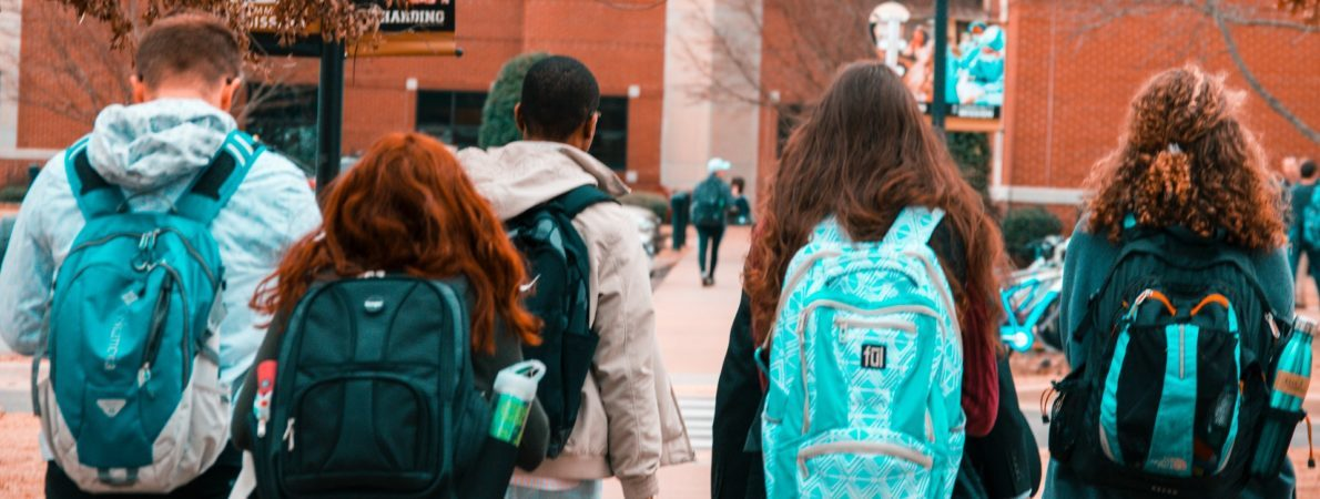 Five students walking to college with backpacks on.