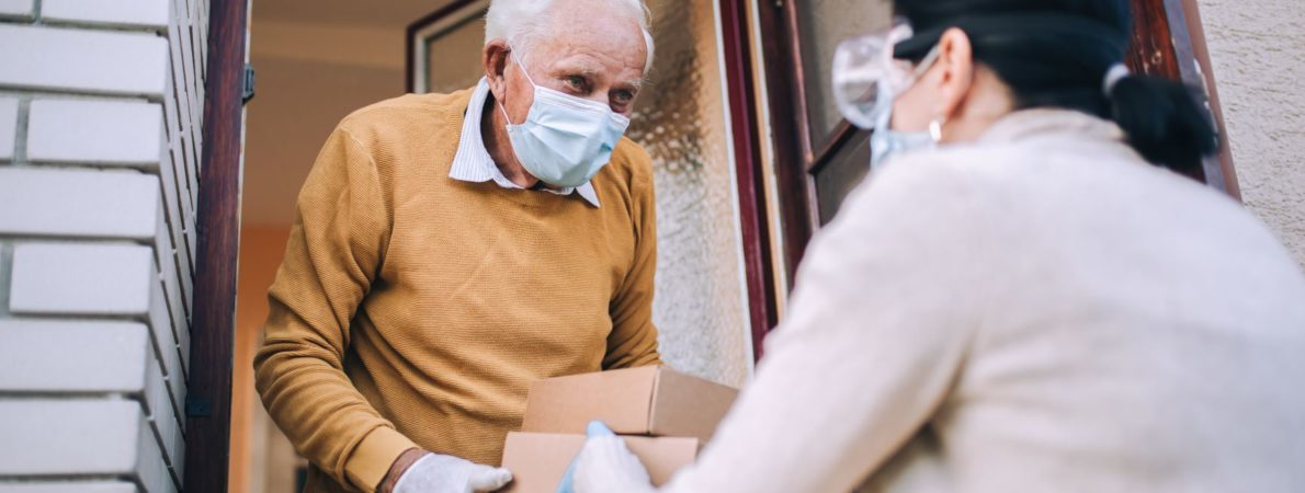 Elderly man receiving home delivery. Both people wear masks.