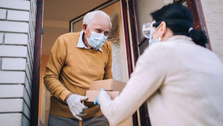 Elderly man receiving home delivery. Both people wear masks.
