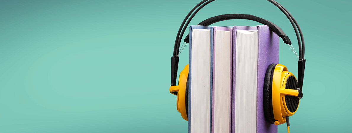 Yellow headphones over two books on a green background