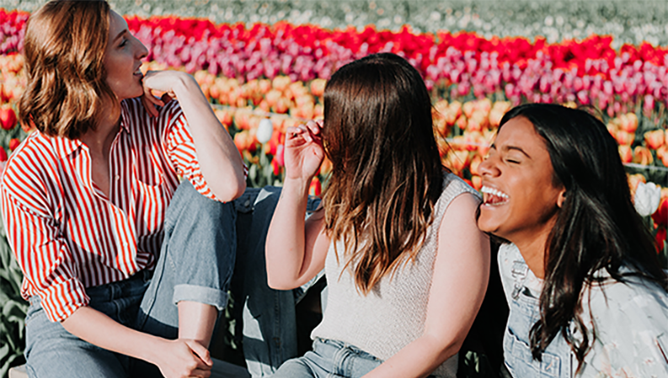three young women sat on a bench, one woman is laughing, there is a field flowers in the background