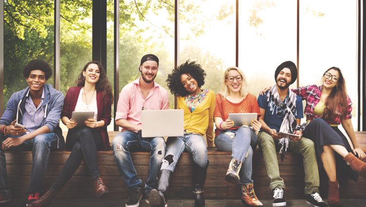 Group of diverse young people sitting on a bench smiling.