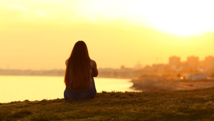 Girl look across a bay at sunset