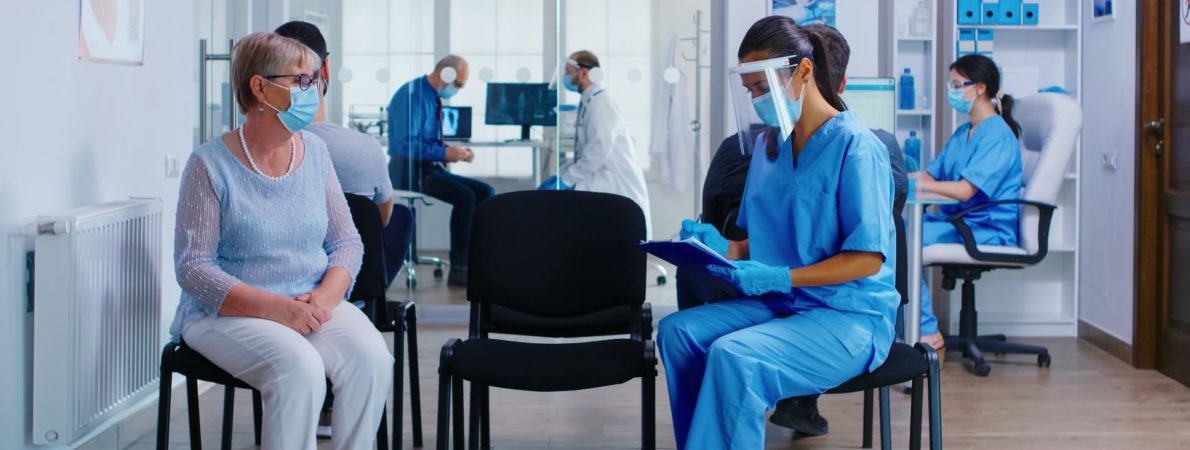 Hospital waiting room. Patient wearing a mask sits across from a nurse wearing a visor.