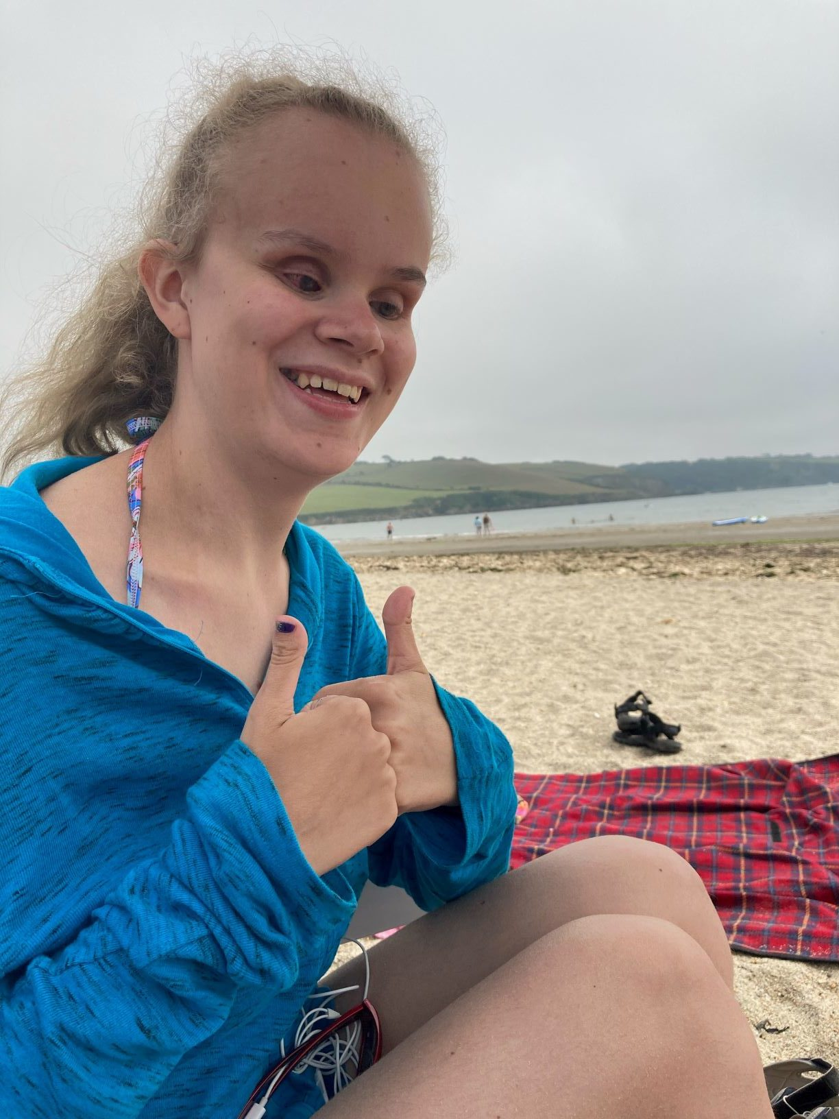 Martha Page smiling on a beach with a thumbs up