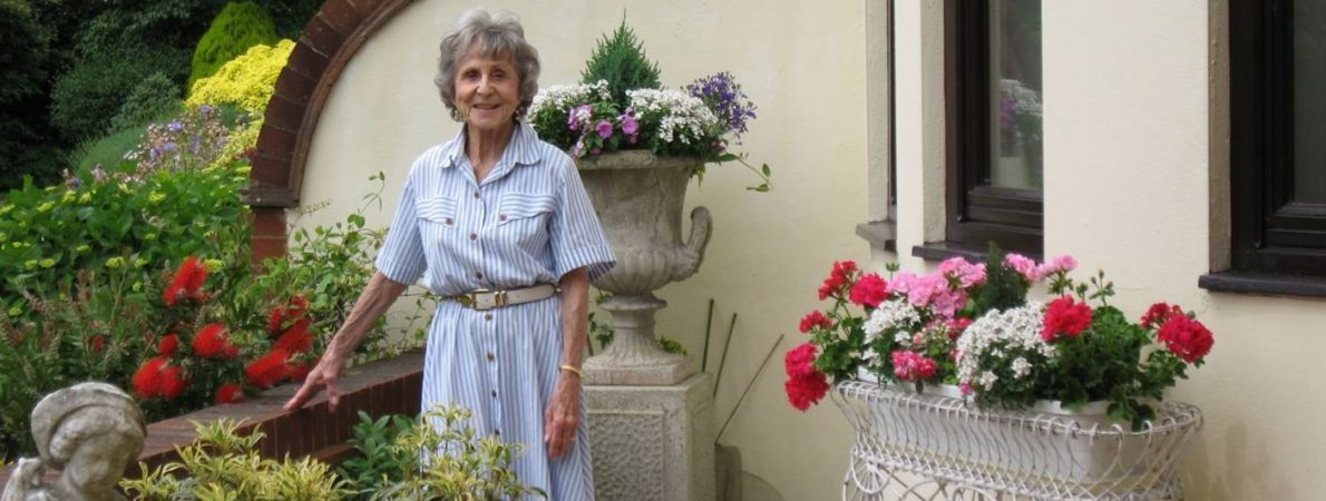 Patricia Powell stood in a garden with bots of brightly coloured flowers around her.