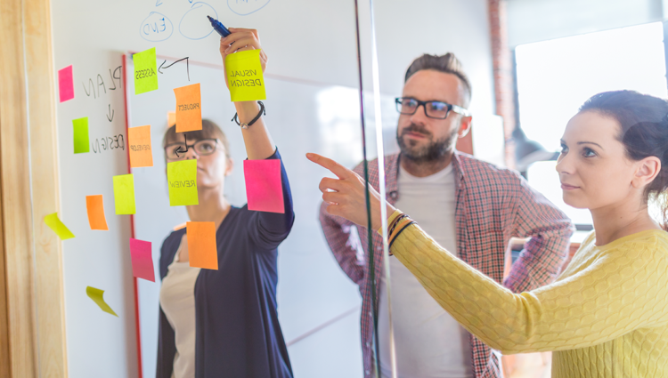 Three people in a meeting, brainstorming ideas using post-its on a clear screen