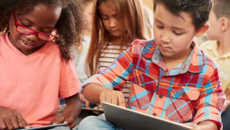 Children sitting down using tablet devices