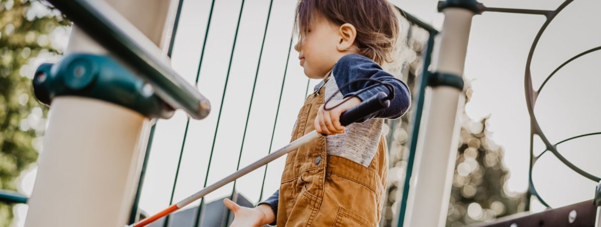 Child with white cane on play equipment