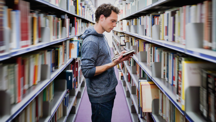 Male student standing in library reading a book