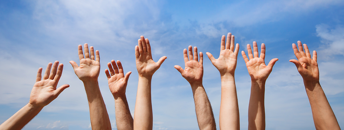 Four pairs of hands raised towards a blue sky.