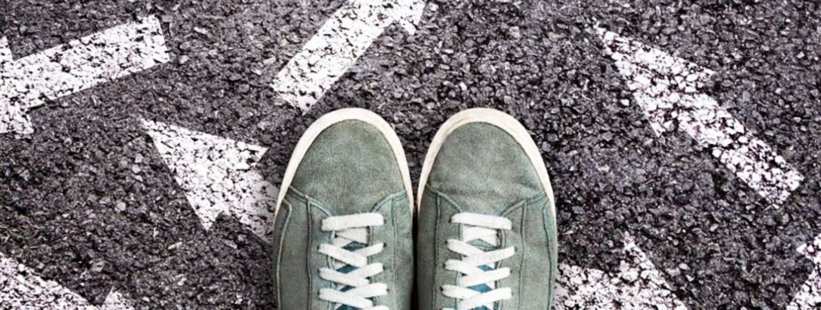 Pair of green trainers standing on white arrows on the road