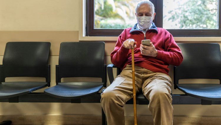 Elderly man wearing a face mask and carrying a stick sits in a hospital waiting room.