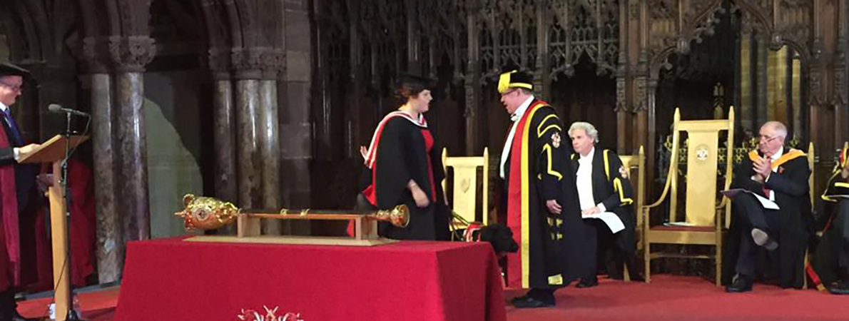 Elin and Jazzy on stage receiving degree from vice chancellor