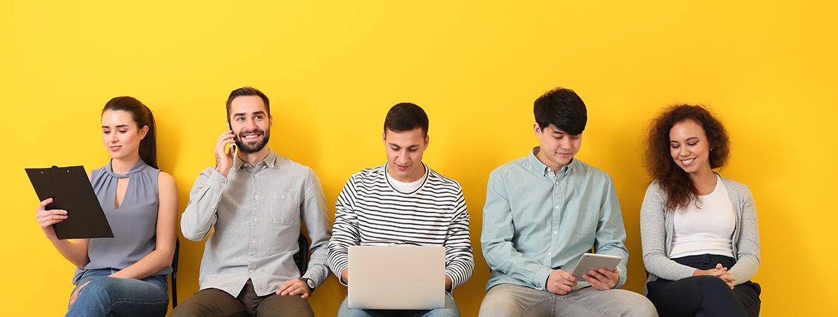 Five young people sat on chairs in a row in front of a bright yellow wall.
