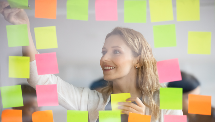 Woman smiling removing post-it notes from a window