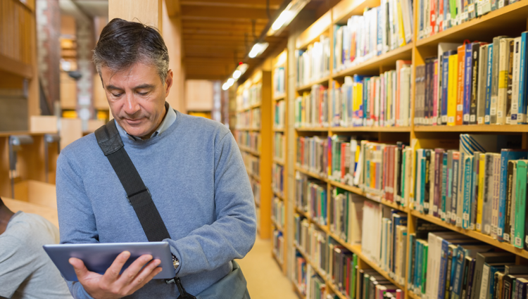 older male looking a an ipad in a university library