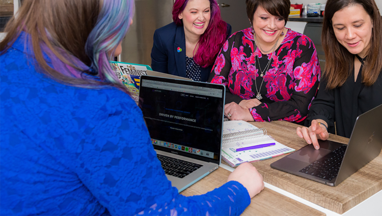 Four women dressed in business wear looking at the same laptop