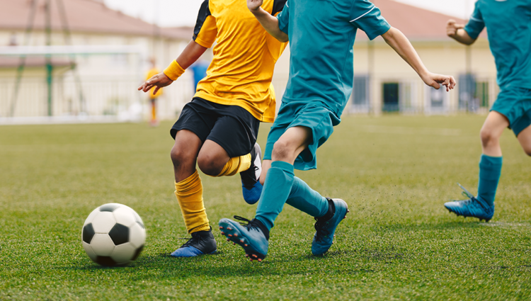 Close up of boys playing football. One is in a yellow football strip, the other in blue