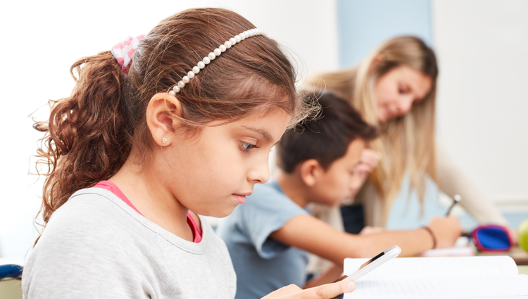 Girl in class looking at her notebook. There is a teacher in the background talking to a child.
