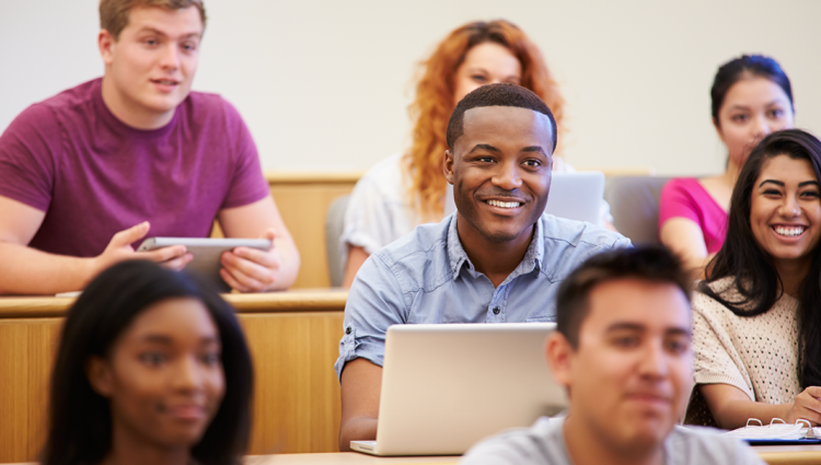 Students in a lecture theatre smiling using laptops