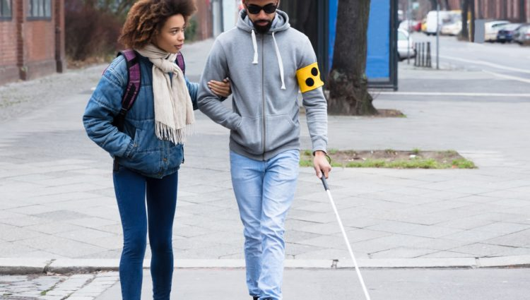 Young woman helping young blind man. The man is holding a stick.