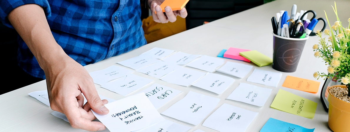 Man holding placing post-it notes on a table