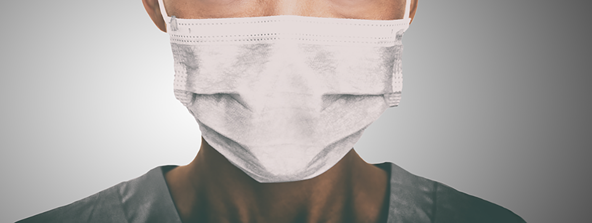 Close up of person wearing a surgical mask.